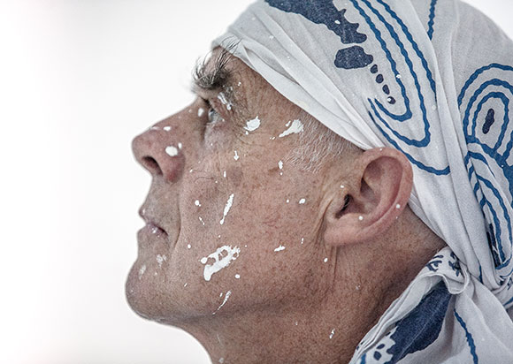 portrait of Richard Long, wearing a headscarf, with his face spattered in white paint